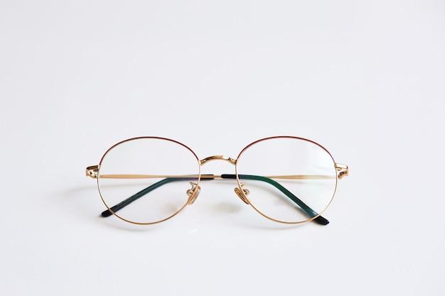 Abgerundete weinlesegläser lokalisiert auf weißem hintergrund. werbefoto der abgerundeten metallbrille mit schatten. optisches modekonzept. nur retro-brille am weißen hintergrund