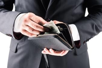 Abgeschnittene Ansicht des Geschäftsmannes im schwarzen Anzug, der Geldbörse mit Dollarbanknoten hält