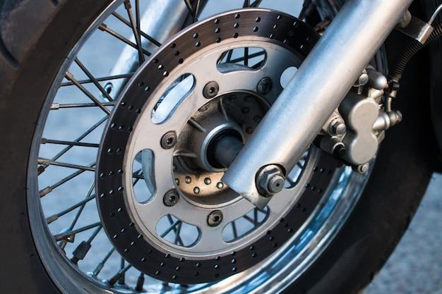 Abgeschnittene aufnahme der aufnahme der motorradgabeln, des reifens und des vorderrads. scheibenbremsanlage an einem motorrad. freiheit und reisekonzept.