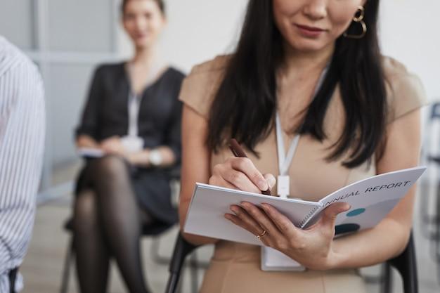 Abgeschnittene aufnahme einer asiatischen jungen frau, die sich notizen macht, während sie auf einer geschäftskonferenz oder auf einem seminar im publikum sitzt, platz kopieren