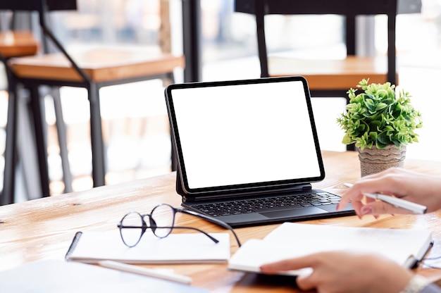 Abgeschnittene aufnahme einer frauenhand, die an einem tablet mit tastatur am schreibtisch arbeitet, leerer bildschirm für die produktanzeige oder grafikdesign.