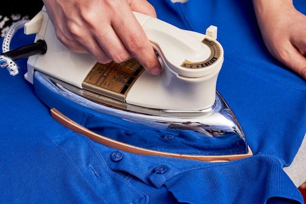 Abgeschnittene aufnahme einer hausfrau, die den blauen pullover bügelt