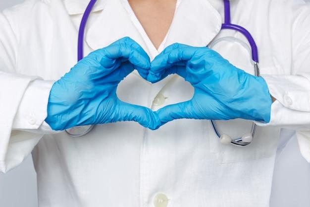 Abgeschnittene aufnahme einer jungen ärztin, die mit ihren händen in blauen handschuhen eine herzform bildet