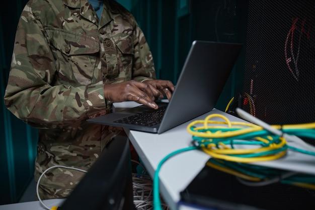 Abgeschnittene aufnahme einer nicht erkennbaren afroamerikanischen frau in militäruniform mit computer beim einrichten des netzwerks im serverraum, kopierraum