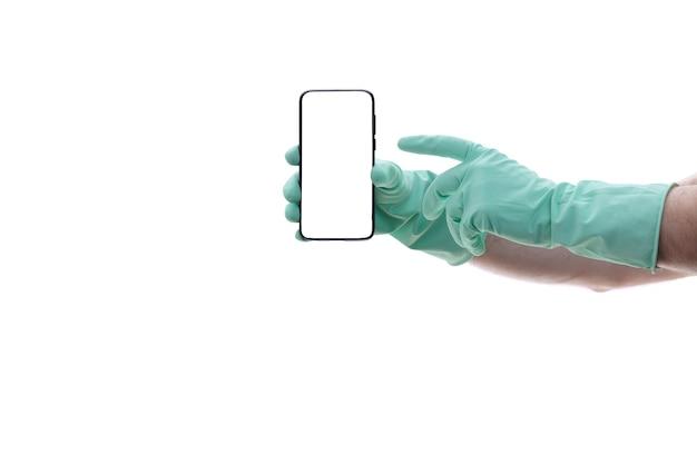 Abgeschnittene aufnahme einer nicht erkennbaren hand des mannes mit grünem latexhandschuh, die einen schwarzen handybildschirm mit weißem leerzeichen für ihren text oder ihr logo zeigt.