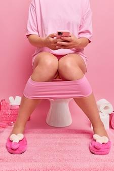 Abgeschnittene aufnahme einer nicht wiedererkennbaren frau benutzt smartphone, während sie auf der toilettenschüssel sitzt, trägt hausschuhe, die auf den beinen heruntergezogen sind, posen in der toilette, die süchtig nach modernen technologien rosa wand ist