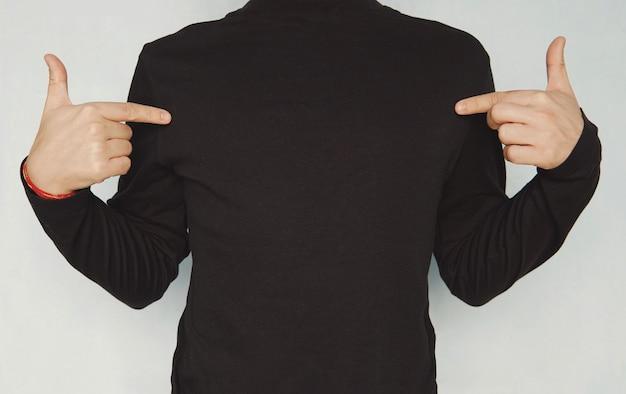 Abgeschnittene aufnahme eines gut aussehenden jungen unrasierten mannes, der freizeitkleidung trägt und mit dem finger auf den kopierraum auf seinem schwarzen leeren t-shirt zeigt. kleidung, design, stil, mode und werbekonzept.
