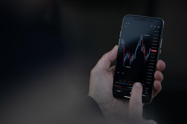 Abgeschnittene aufnahme eines händlers, der investitionen verwaltet und aktien in der mobilen app handelt, männliche hand, die smartphone-bildschirmanzeige mit finanzdiagramm berührt. börsenmarkt und online-handel-konzept
