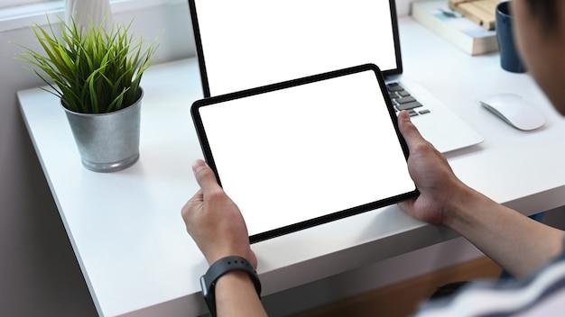 Abgeschnittene aufnahme eines jungen mannes, der ein digitales tablet mit weißem bildschirm hält und einen computer-laptop im heimbüro verwendet.