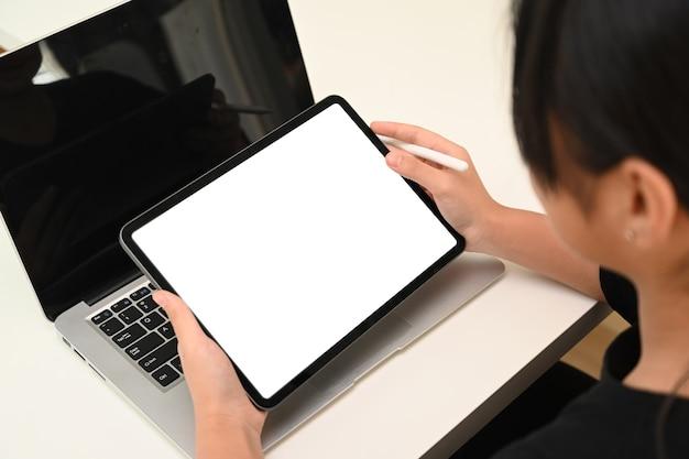 Abgeschnittene aufnahme eines jungen schulmädchens, das online mit laptop-computer lernt und handy-suchinformationen verwendet.