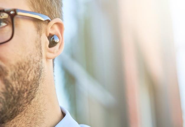 Abgeschnittene aufnahme eines kaukasischen mannes, der schwarze drahtlose kopfhörer trägt und musik hört