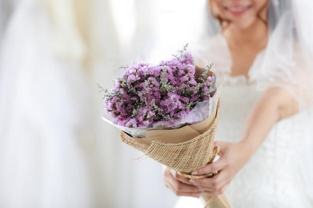 Abgeschnittene aufnahme eines lila hochzeitsblumenstraußes, der in den händen einer nicht erkennbaren braut im weißen kleid mit durchsichtigem haarschleier gehalten wird und lächelnder blick in die kamera in unscharfem hintergrund in der umkleidekabine steht.