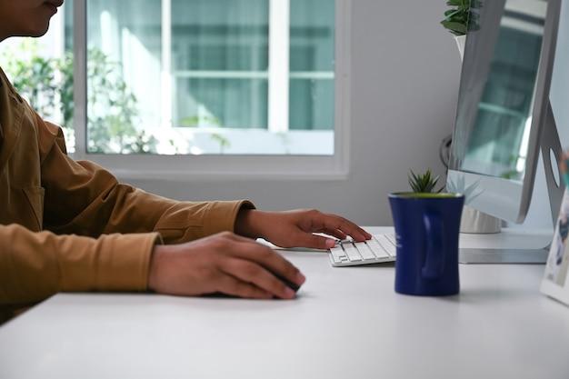 Abgeschnittene aufnahme eines mannes, der einen computer verwendet, der an seinem schreibtisch im büro an einer neuen projektidee arbeitet.
