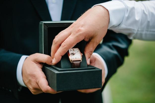Abgeschnittene aufnahme eines mannes, der einen eleganten anzug trägt und eine armbanduhr hält. mannhand mit eleganter teurer luxusuhr mit lederarmband auf naturhintergrund.