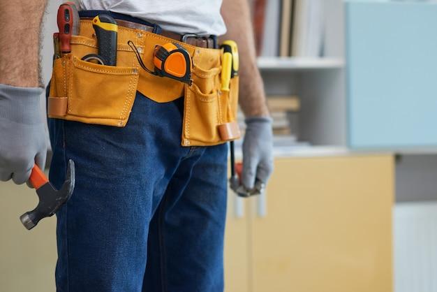 Abgeschnittene aufnahme eines professionellen mechanikers, der einen werkzeuggürtel mit einem hammer und einem verstellbaren trägt