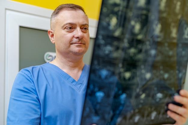 Abgeschnittene aufnahme eines radiologen, der die röntgendiagnose untersucht, während er in der nähe des ct-scannerraums im krankenhaus steht.