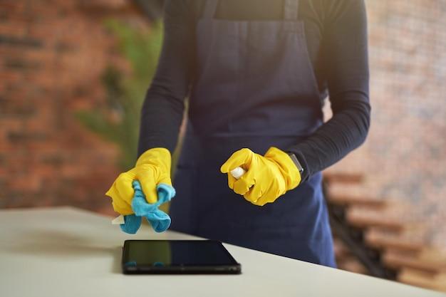 Abgeschnittene aufnahme eines reinigungsdienstes in gummihandschuhen und uniform mit antibakteriellem desinfektionsmittel