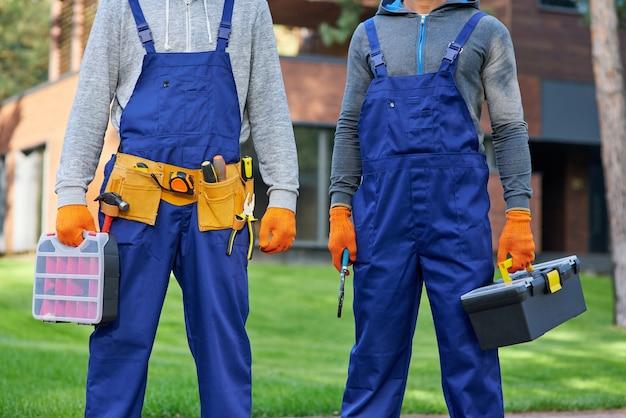 Abgeschnittene aufnahme von zwei männlichen baumeistern in blauen overalls mit werkzeugkasten auf der baustelle