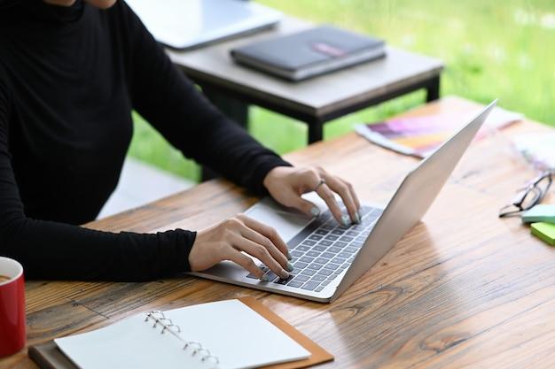 Abgeschnittene erschossene designerin, die mit laptop-computer an ihrem schreibtisch arbeitet.
