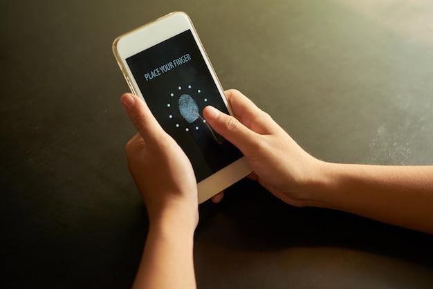 Abgeschnittene hände, die den finger auf den identifikationspunkt auf dem touchscreen legen