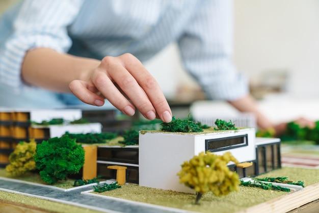 Abgeschnittene junge architektin, die entwurf mit hausmodell am arbeitsplatz entwirft