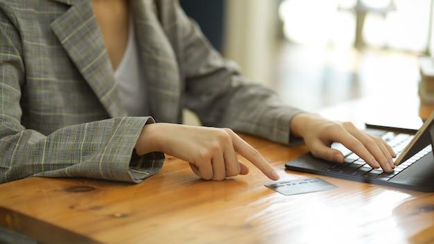 Abgeschnittene nahaufnahme hände bild frau mit tablet für online-zahlung überweisung geld kreditkarte