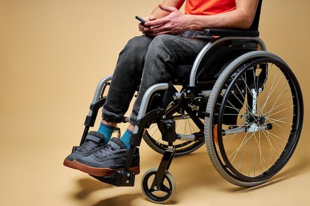 Abgeschnittener behinderter mann, der auf rollstuhl mit smartphone sitzt und mit jemandem plaudert. isolierter beiger hintergrund