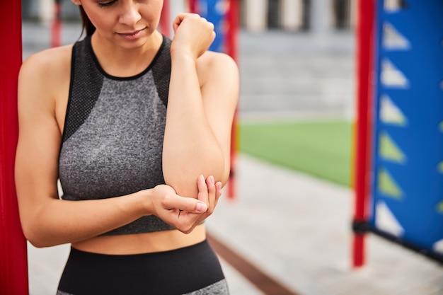 Abgeschnittener kopf einer schlanken athletischen frau, die auf dem sportplatz steht und den arm berührt, während sie sich verletzt