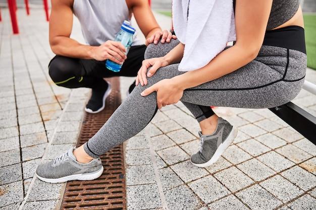 Abgeschnittener kopf einer schlanken frau, die auf einem sportplatz sitzt, nachdem sie das knie verletzt hat und der mann sich um sie gekümmert hat