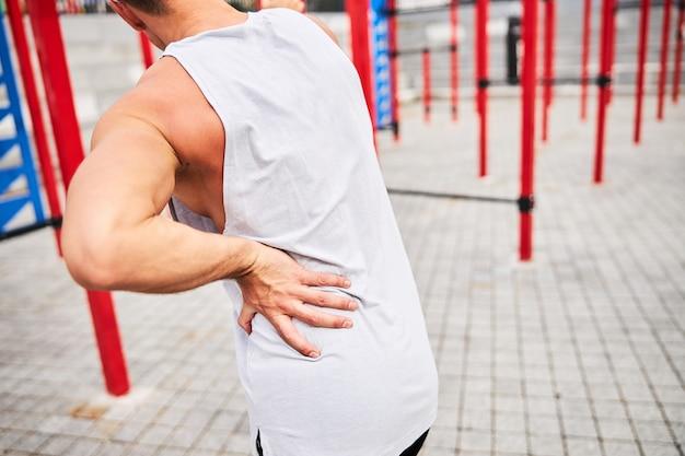 Abgeschnittener kopf eines athletischen jungen mannes, der nach dem training mit reckstangen auf dem sportplatz rückenschmerzen verspürt