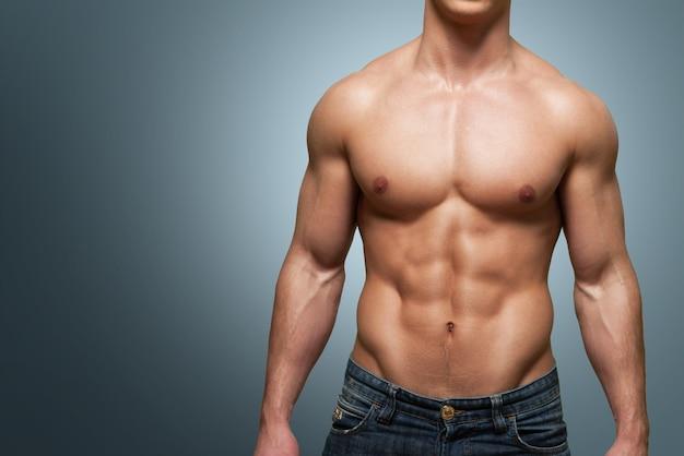 Abgeschnittenes bild des fitten muskulösen körpers eines sportlers