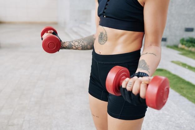 Abgeschnittenes bild einer fitten, starken jungen frau, die im freien übungen mit hanteln macht, wenn sie an ihren armmuskeln arbeitet