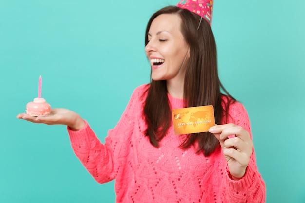 Abgeschnittenes bild einer frau in einem gestrickten rosa pullover, einem geburtstagshut, der eine kreditkarte in der hand hält, und einen kuchen mit kerze einzeln auf blauem türkisfarbenem wandhintergrund. menschen lifestyle-konzept. kopieren sie platz.