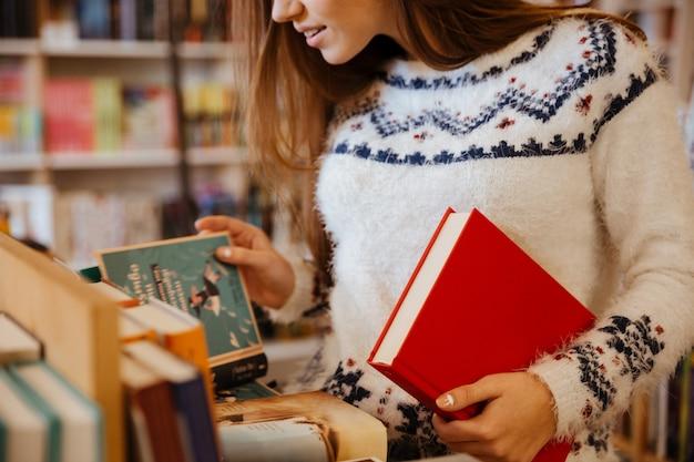 Abgeschnittenes bild einer jungen frau, die bücher in der bibliothek auswählt