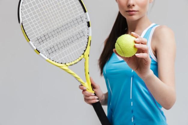 Abgeschnittenes bild einer selbstbewussten tennisspielerin mit schläger und ball isoliert über grauer wand
