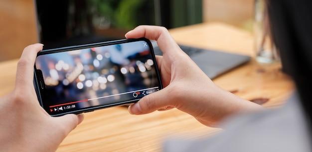 Abgeschnittenes bild einer weiblichen hand, die smartphone hält und videos ansieht, während sie im freien steht.