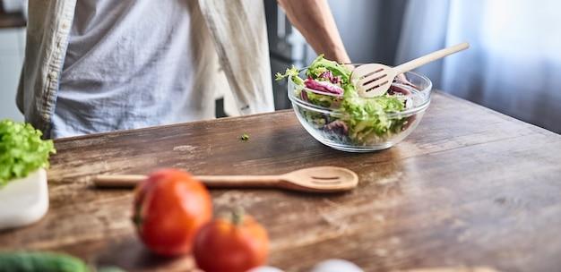 Abgeschnittenes bild eines attraktiven jungen mannes kocht in der küche. salat machen. gesundes lebensstilkonzept.