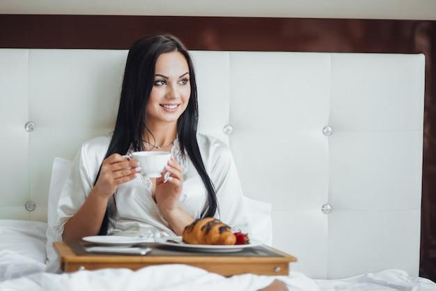 Abgeschnittenes bild eines glücklichen brünetten mädchens, das mit einem rosenstrauß in ihrem bett sitzt und morgens croissant mit kaffee auf einem tablett isst