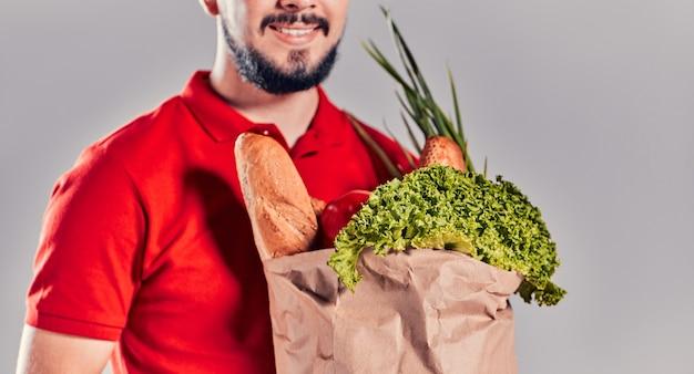 Abgeschnittenes bild eines jungen bärtigen kuriers in einem roten t-shirt und einer mütze mit einem lebensmittelpaket. essen nach hause liefern.