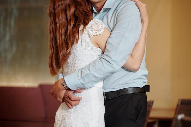 Abgeschnittenes bild eines jungen freundes und einer freundin, die sich umarmen und küssen und genießen, zeit miteinander zu verbringen?
