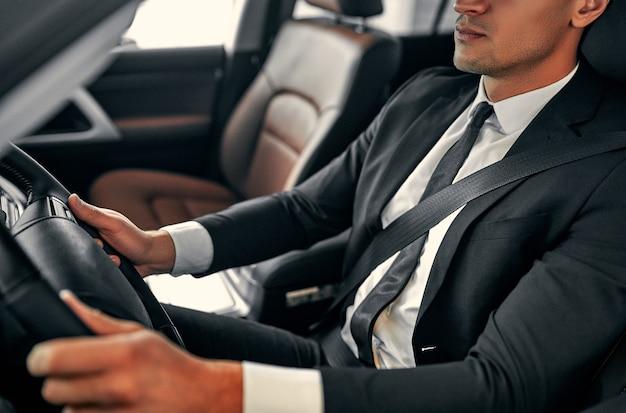 Abgeschnittenes bild eines jungen gutaussehenden geschäftsmannes sitzt im luxusauto. ernster mann im anzug fährt.
