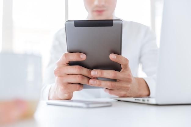 Abgeschnittenes bild eines jungen mannes in weißem hemd mit tablet-computer. coworking.