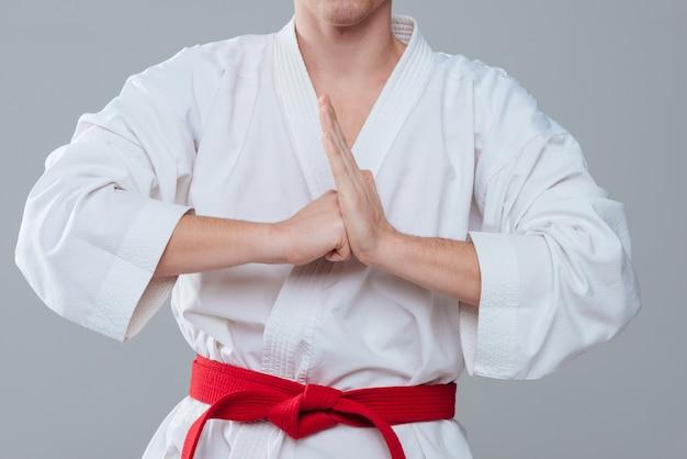 Abgeschnittenes bild eines jungen sportlers im kimono, der mit den händen auf grauem hintergrund gestikuliert.