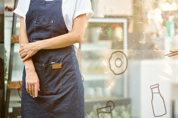 Abgeschnittenes bild eines kleinen lebensmittelladenbesitzers in jeansschürze, der am eingang steht und auf kunden wartet
