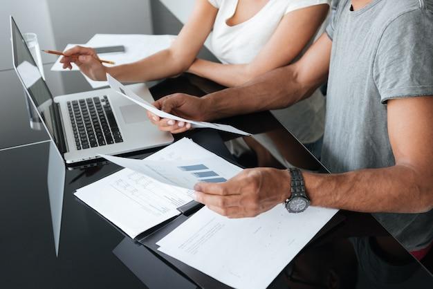 Abgeschnittenes bild eines liebevollen jungen paares, das laptop verwendet und seine finanzen mit dokumenten analysiert.