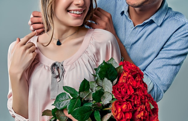 Abgeschnittenes bild eines schönen romantischen paares in der liebe isoliert auf grauem hintergrund. gut aussehender mann trägt halskette auf seiner attraktiven jungen frau. alles gute zum valentinstag!
