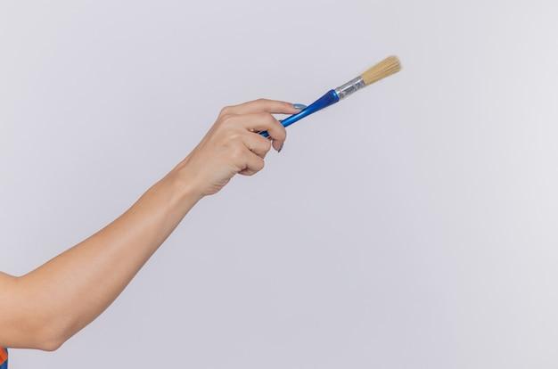 Abgeschnittenes foto der hand der frau, die pinsel hält