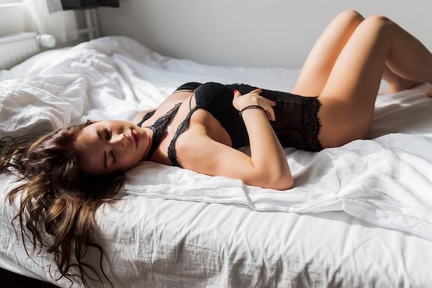 Abgeschnittenes foto der hüften einer attraktiven jungen frau, die in schwarzen dessous mit strümpfen, schnürsenkeln tragen. seitwärts. erotisches damenmodekonzept.