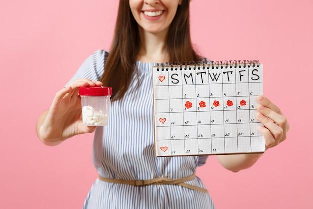 Abgeschnittenes foto einer frau im blauen kleid, die eine flasche mit weißen pillen hält, kalender für die weibliche periode, die menstruationstage einzeln auf hintergrund überprüft. gynäkologisches konzept des medizinischen gesundheitswesens. platz kopieren.