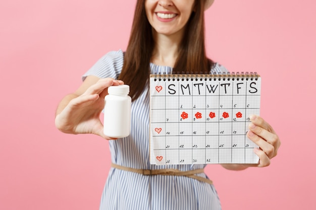 Abgeschnittenes foto einer frau im blauen kleid, die weiße flasche mit pillen hält, kalender für weibliche perioden, überprüfung der menstruationstage einzeln auf hintergrund. gynäkologisches konzept des medizinischen gesundheitswesens. platz kopieren.